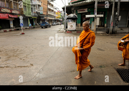 monks and novice on their daily alms round , mae sot town, early morning , northern thailand - Stock Photo