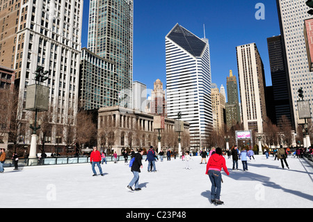 Skaters circle the ice rink in Millennium Park with the Smurfit-Stone Building. Chicago, Illinois, USA. - Stock Photo
