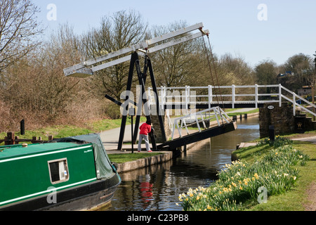 Froncysyllte, North Wales, UK. Woman raising Fron lift bridge at 28W for approaching narrowboat on Llangollen canal - Stock Photo