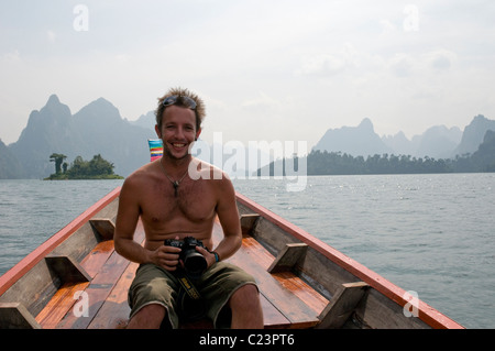 Tourist in a Long-Tail boat, Cheow Larn Lake, Khao Sok National Park, Southern Thailand - Stock Photo