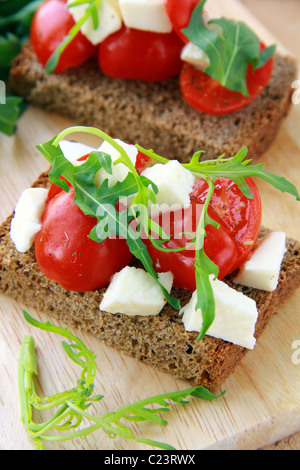 sandwich with mozzarella and tomatoes on rye bread of Italian style - Stock Photo