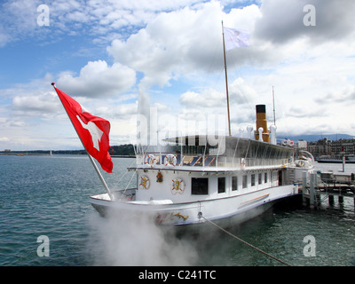 famous paddle steamboat on lake Geneva anchored in front of city Geneva releasing steam with swiss flag - Stock Photo
