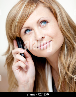 Thoughtful businesswoman talking on phone in her office - Stock Photo