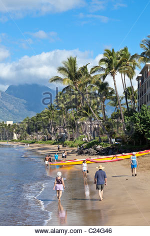 Morning walk past yellow outrigger canoe on Sugar Beach at Kihei on the island of Maui in the State of Hawaii USA - Stock Photo