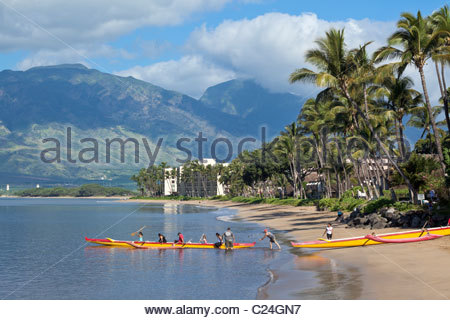 Outrigger canoe setting out for morning paddle from Sugar Beach at Kihei on the island of Maui in the State of Hawaii - Stock Photo