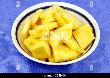 Pieces of exotic ripe yellow golden fruit in a white bowl with a pretty blue background. Sweet yellow pineapple - Stock Photo