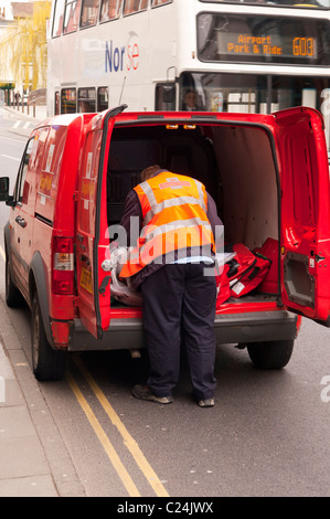 A Royal Mail postman getting mail from his van in Norwich , Norfolk , England , Britain , Uk - Stock Photo