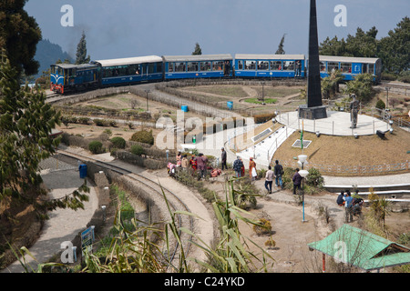The toy train passes through Batasia loop and the war memorial in Darjeeling, West Bengal, India. - Stock Photo