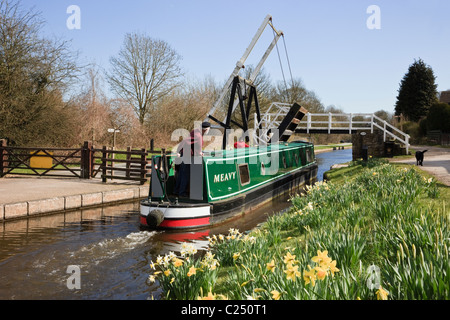 Froncysyllte, North Wales, UK. Green narrowboat approaching Fron lift bridge at 28W on the Llangollen canal in spring - Stock Photo