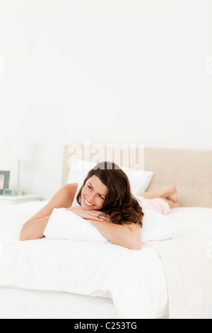 Pensive woman lying on his bed during a morning - Stock Photo