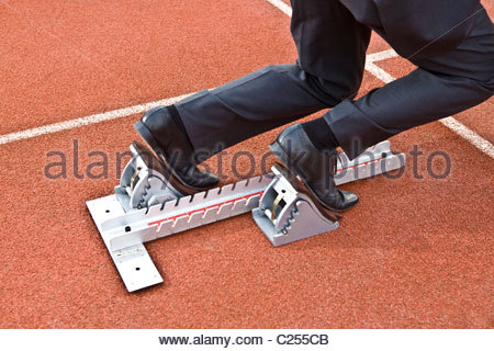 Businessman on the starting blocks of a running track. - Stock Photo