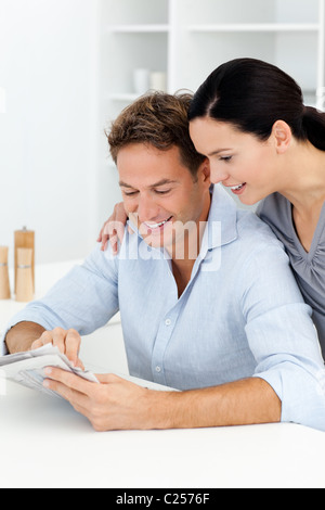 Lovely couple looking at something on the newspaper - Stock Photo