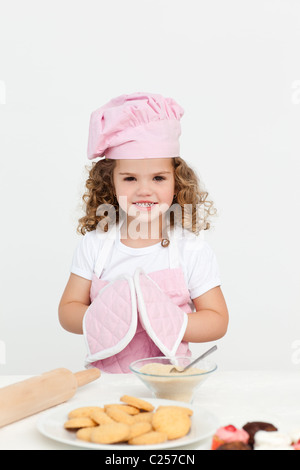 Cute girl with kitchen gloves while preparing cookies - Stock Photo