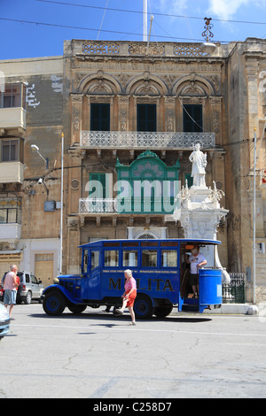 malta, mediterranean, blue maltese tour bus standing in front of a traditional colonial building in a town centre - Stock Photo