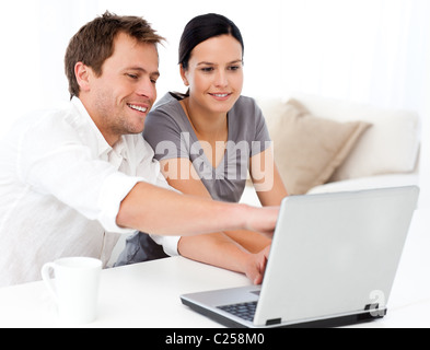Cute man showing something on the laptop screen to his girlfriend - Stock Photo