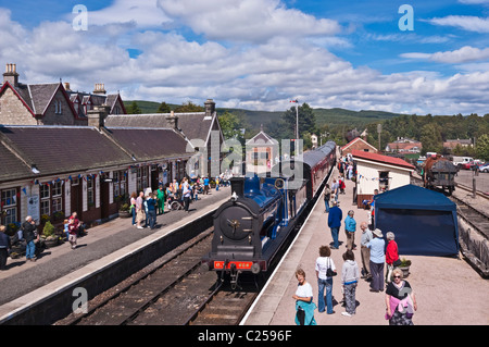 Ex. Caledonian Railway steam engine 828 arriving at Boat of Garten railway station from Broomhill in Strathspey - Stock Photo