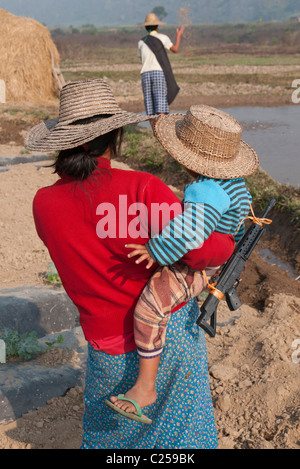 Mother and child with toy gun in field. Hsipaw. Northern Shan State. Myanmar - Stock Photo