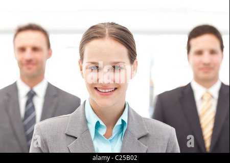 Cheerful businesswoman standing in front of two businessmen - Stock Photo