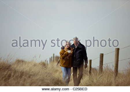A senior couple walking along a path together - Stock Photo