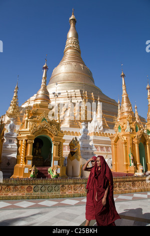 The biggest Buddhist temple Shwedagon pagoda with walking monks, Rangoon, Burma. - Stock Photo