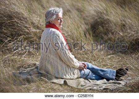 A senior woman sitting amongst the sand dunes - Stock Photo
