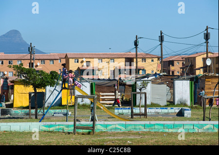 A playground with shacks and new housing along Vanguard Drive, Epping, Cape Town, South Africa - Stock Photo