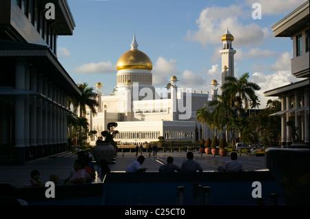 The Sultan Omar Ali Saifuddien Mosque, Bandar Seri Begawan, Brunei, through shopping centre buildings and people - Stock Photo