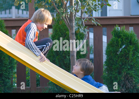 Brothers stopping for conversation on backyard slide age 8 and 5. St Paul Minnesota MN USA - Stock Photo