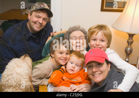 Three generations and Gunner the dog enjoying a birthday portrait with great grandma age 93. Clitherall Minnesota - Stock Photo