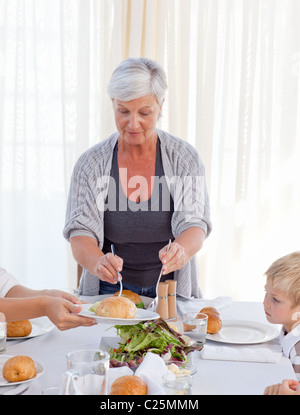 Grandmother giving other family members some food during the meal - Stock Photo
