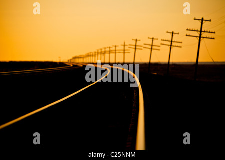 Endless line of telephone poles along rail road tracks at sunrise Imperial Valley, CA. - Stock Photo