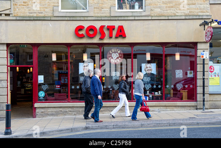 People walk past a branch of Costa Coffee - Stock Photo