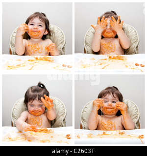 Happy baby having fun eating messy showing hands covered in Spaghetti Angel Hair Pasta red marinara tomato sauce. - Stock Photo