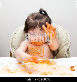 Happy baby having fun eating messy slapping hands covered in Spaghetti Angel Hair Pasta red marinara tomato sauce. - Stock Photo