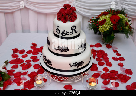 Chocolate wedding cake with red roses petals and candles at head table - Stock Photo