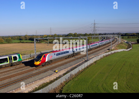 A Virgin Pendolino heads a Glasgow bound service north through Litchfield Trent Vallet while a London Midland stopper - Stock Photo