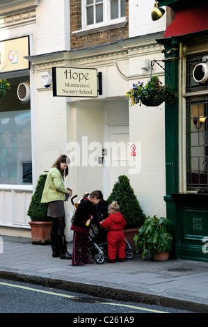 Mother and children outside Hope Montessori Nursery School Marylebone London England UK