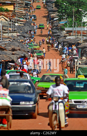 Red dirt road in the town of Man, Ivory Coast, West Africa - Stock Photo