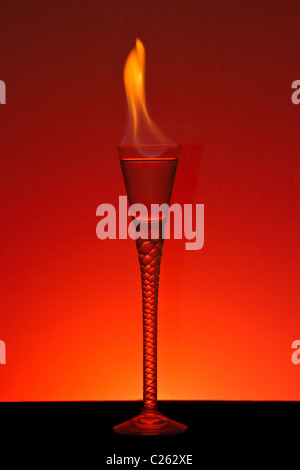 Alcohol burning in beautiful handmade glass with burning red background - Stock Photo