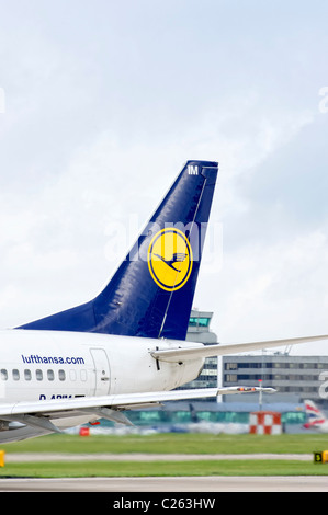 Tail fin of a Lufthansa aircraft as it prepares for take off - Stock Photo