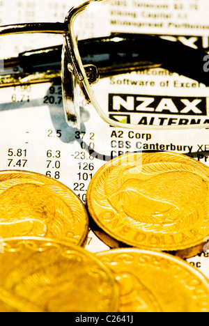 Glasses and New Zealand coins on share price listing pages - cross processed effect - Stock Photo