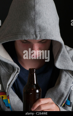 Teenaged boy in hoody and drinking - Stock Photo