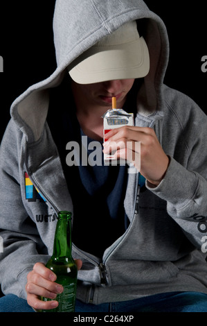 Teenaged boy in hoody smoking and drinking - Stock Photo