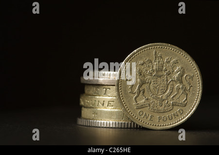 A stack of British coins with a pound coin standing on it`s edge. - Stock Photo