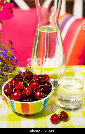 Bowl with fresh cherries in the garden - Stock Photo