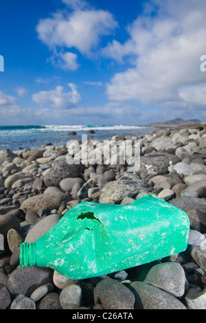 An old oil bottle lying on a rocky shore. Nice shot for biodegradable or environment concepts. - Stock Photo