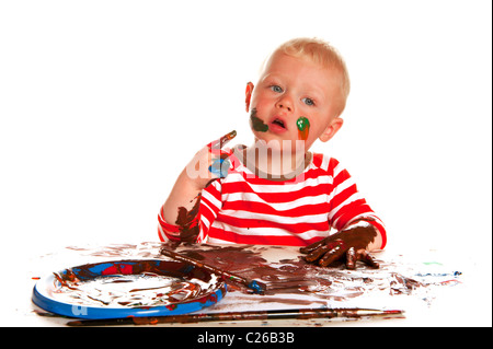 Little boy is painting and making a mess - Stock Photo