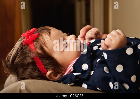 a profile of a baby girl lying on her father's lap - Stock Photo