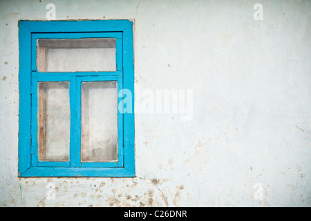 Old cracked wall with window painted with blue - Stock Photo