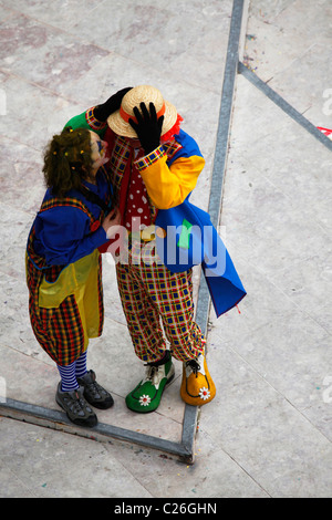 A man and a woman dressed as two clowns chat closely during the Mardi Gras carnival parade. - Stock Photo